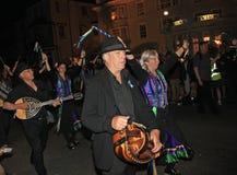 SIDMOUTH, DEVON, INGLATERRA - 10 DE AGOSTO DE 2012: Um grupo de músicos e os dançarinos da obstrução vestidos no malva e no verde foto de stock