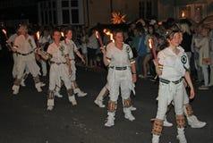 SIDMOUTH, DEVON, INGLATERRA - 10 DE AGOSTO DE 2012: Um troup de dançarinos de Morris da jovem senhora guarda suas tochas flamejan foto de stock