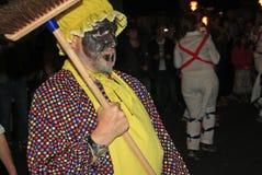 SIDMOUTH, DEVON, INGLATERRA - 10 DE AGOSTO DE 2012: Un hombre con una escoba y un delantal amarillo lleva un troup de Morris ingl foto de archivo libre de regalías