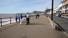 Sidmouth promenade seafront Devon people walking stock footage