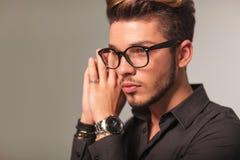 Sidocloseupstående av en ung man med att be för exponeringsglas Arkivbilder