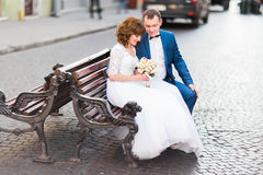 Sidofoto av de gladlynta nygifta personerna som sitter på bänken och innehavet bröllopbuketten royaltyfri bild