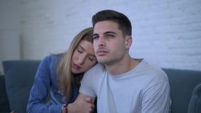 Sidopannaskott av unga attraktiva par med frustrerat för pojkvän ledset och deprimerat hemmastatt trösta för soffa och för flickv lager videofilmer