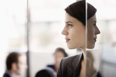 Sidoprofil på en affärskvinna med coworkers i bakgrunden arkivfoto