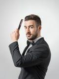 Sidoprofilsikt av den unga mannen som kammar hår som ser kameran royaltyfri foto