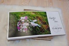 Sidor av bröllopphotobook eller bröllopalbumet på matta på trä Royaltyfri Bild