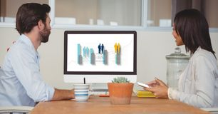 Sidosikt av affärsfolk som ser grafen på datorskärmen, medan sitta i regeringsställning Arkivbild