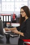 Sidosikt av affärskvinnan på skrivbordet Fotografering för Bildbyråer