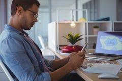 Sidosikt av affärsmannen som använder mobiltelefonen på det idérika kontoret fotografering för bildbyråer