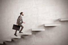 Sidosikt av affärsmannen som klättrar en konkret trappa royaltyfri fotografi
