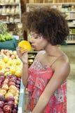 Sidosikt av afrikansk amerikankvinnan som luktar den nya apelsinen på supermarket arkivfoton