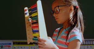 Sidosikt av afrikansk amerikanskolflickan med anblicken som lär matematik med kulrammet i klassrumet 4k arkivfilmer