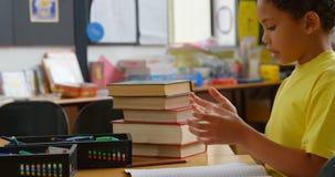 Sidosikt av afrikansk amerikanskolpojken som räknar med hans finger på skrivbordet i ett klassrum på skola 4k arkivfilmer
