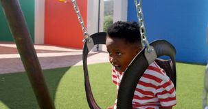 Sidosikt av afrikansk amerikanskolpojken som spelar på en gunga i skolalekplatsen 4k stock video