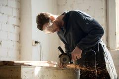 Sidosikt av arbetaren som använder vinkelmolar för metallklipp arkivfoto