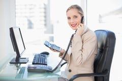Sidosikt av att le den blonda affärskvinnan på telefonen Fotografering för Bildbyråer