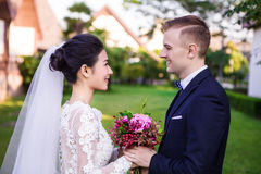 Sidosikt av att le den hållande buketten för brölloppar på gräsmatta royaltyfria bilder