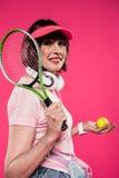 Sidosikt av att le den tennisracket och bollen för kvinna hållande och att se kameran royaltyfri fotografi