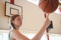Sidosikt av basketspelaren som balanserar bollen på fingret Fotografering för Bildbyråer