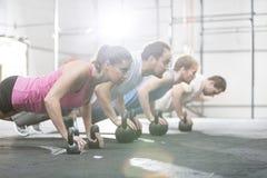 Sidosikt av beslutsamt folk som gör liggande armhävningar med kettlebells på crossfitidrottshallen Royaltyfri Fotografi