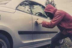 Sidosikt av bilen som tvingas av en man i hoodie och maskering Tjuven försöker att stjäla medlet från en parkering Unga manliga h royaltyfria foton