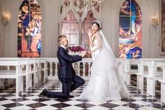 Sidosikt av brudgummen som sätter cirkeln på förvånade bruds finger i kyrka royaltyfri fotografi
