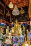 Sidosikt av Buddha som är ordförande i kunglig prästvigningkorridor på Wat Poramaiyikawas Worawihan arkivfoton