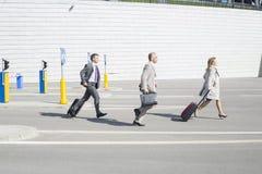 Sidosikt av businesspeople med bagage som går på gatan Royaltyfria Foton