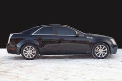 Sidosikt av Cadillac CTS i svart f?rg, n?r att ha gjort ren f?r f?rs?ljning i en bakgrund f?r vinterdag p? parkering ovanf?r den  royaltyfri foto