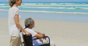 Sidosikt av den aktiva höga afrikansk amerikankvinnan med den rörelsehindrade höga mannen på stranden i solsken 4k lager videofilmer