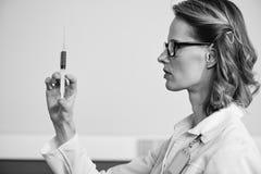 Sidosikt av den allvarliga kvinnadoktorn i glasögon som rymmer injektionssprutan Royaltyfri Foto