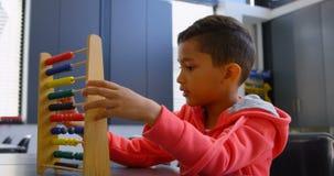Sidosikt av den asiatiska skolpojken som löser matematikproblem med kulrammet på skrivbordet i ett klassrum på skola 4k stock video