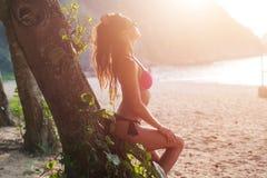 Sidosikt av den attraktiva slanka unga kvinnan i bikinibenägenhet mot trädet som rymmer hennes bruna hår tillbaka med en hand arkivbild