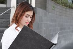 Sidosikt av den attraktiva unga asiatiska affärskvinnan som i regeringsställning ser skrivbordsarbete i dokumentmapp på gångbanan Fotografering för Bildbyråer