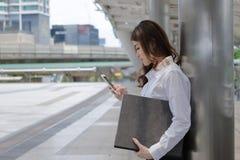 Sidosikt av den attraktiva unga asiatiska mappen och att se för dokument för innehav för affärskvinna den mobila smarta telefonen royaltyfri fotografi