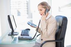 Sidosikt av den blonda affärskvinnan på telefonen Arkivfoto