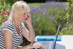 Sidosikt av den blonda kvinnan som utomhus kallar Arkivbilder