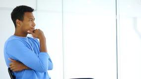 Sidosikt av den eftertänksamma Afro--amerikan mannen som ser till och med kontorsfönster Royaltyfri Foto