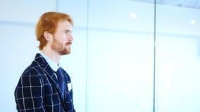 Sidosikt av den eftertänksamma rödhårig manaffärsmannen Looking till och med kontorsfönster Royaltyfri Bild