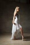 Sidosikt av den eleganta ballerina som poserar i vit i pointes Arkivfoto
