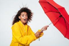 Sidosikt av den förvirrade förvånade afrikanska kvinnan i regnrock Royaltyfri Bild