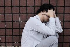 Sidosikt av den frustrerade deprimerade unga asiatiska affärsmannen som täcker framsidan med händer arkivbild