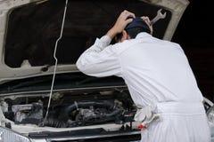 Sidosikt av den frustrerade stressade unga mekanikermannen i den vita likformign som trycker på hans huvud med händer mot bilen i Royaltyfri Foto