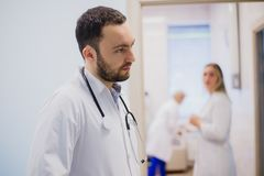 Sidosikt av den fundersamma barndoktorn i medicinsk likformig som lyssnar till patienten arkivbild