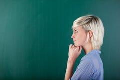 Sidosikt av den fundersamma blonda kvinnan vid den svart tavlan Royaltyfri Bild