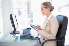 Sidosikt av den gladlynta blonda affärskvinnan som använder räknemaskinen Arkivfoton