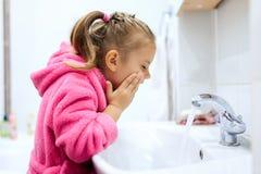 Sidosikt av den gulliga lilla flickan med hästsvansen i den rosa badrocken som tvättar henne händer Royaltyfri Foto