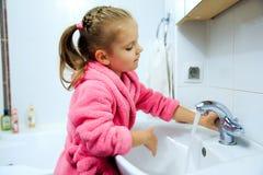 Sidosikt av den gulliga lilla flickan med hästsvansen i den rosa badrocken som tvättar henne händer Fotografering för Bildbyråer