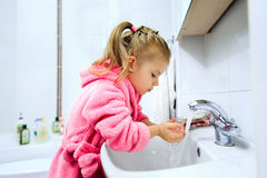 Sidosikt av den gulliga lilla flickan med hästsvansen i den rosa badrocken som tvättar henne händer Arkivfoton