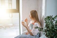 Sidosikt av den härliga avsmakningmuffin för ung kvinna arkivfoto
